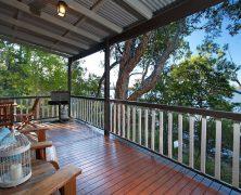 Открытая терраса загородного дома. Материал отделки пола – деревянная доска